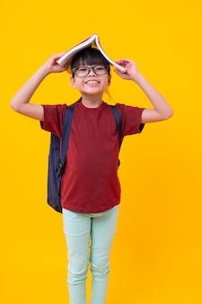 O retrato do miúdo engraçado da menina asiática com o livro na cabeça que sorri, estudante consideravelmente tailandês na camisa vermelha com vidros tem a posição atrativa e a vista, o conhecimento e a sabedoria