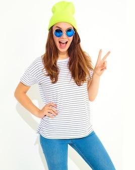 O retrato do modelo à moda novo da mulher no verão ocasional veste-se no chapéu amarelo do gorro isolado no branco. mostrando sinal de paz