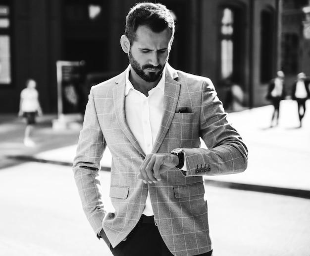 O retrato do modelo considerável do homem de negócios da forma vestiu-se no elegante terno azul. homem posando na rua fundo. metrosexual