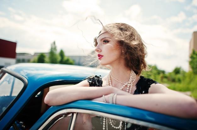 O retrato do modelo de menina bonita moda encaracolado com maquiagem brilhante em estilo retro, inclinou-se sobre uma porta de carro antigo.