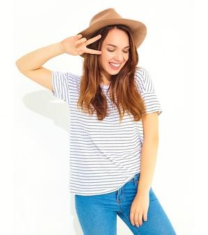 O retrato do modelo de mulher de riso à moda novo no verão ocasional veste-se no chapéu marrom com a composição natural isolada na parede branca. mostrando sinal de paz