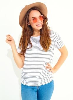 O retrato do modelo de mulher de riso à moda novo no verão ocasional veste-se no chapéu marrom com a composição natural isolada na parede branca.