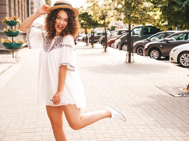 O retrato do modelo de sorriso bonito com o penteado afro das ondas vestiu-se no vestido branco do moderno do verão.
