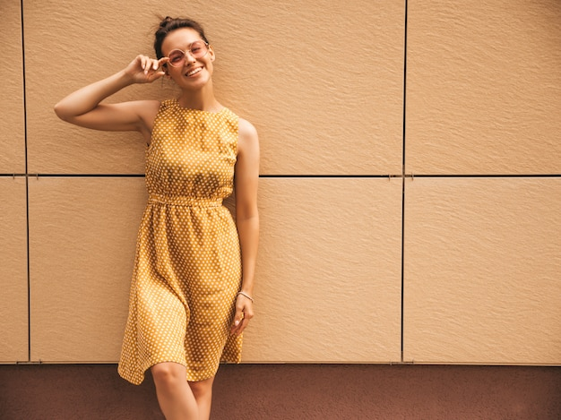 O retrato do modelo de sorriso bonito do moderno vestiu-se no vestido amarelo do verão. menina na moda posando na rua. mulher engraçada e positiva se divertindo