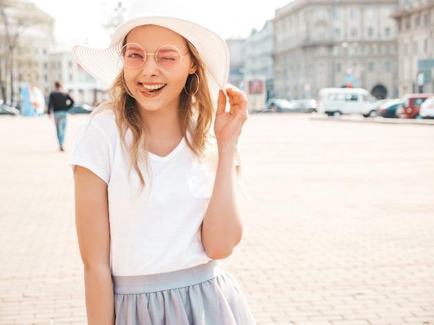 O retrato do modelo louro de sorriso bonito vestiu-se na roupa do moderno do verão. menina na moda posando na rua em óculos de sol redondos. mulher engraçada e positiva se divertindo no chapéu