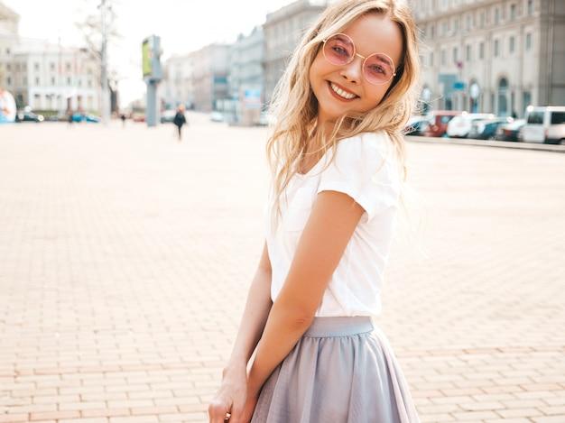 O retrato do modelo louro de sorriso bonito vestiu-se na roupa do moderno do verão. menina na moda posando na rua em óculos de sol redondos. mulher engraçada e positiva se divertindo