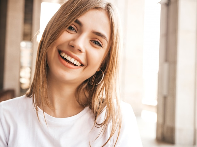 O retrato do modelo louro de sorriso bonito vestiu-se na roupa do moderno do verão.