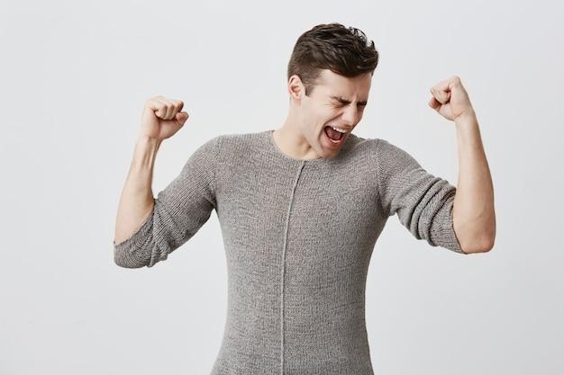 O retrato do modelo masculino entusiasmado e entusiasmado fecha os punhos com prazer, grita de felicidade, comemora sua vitória, tem um grande triunfo. jovem bonito gesticula alegremente dentro de casa. conceito de sucesso