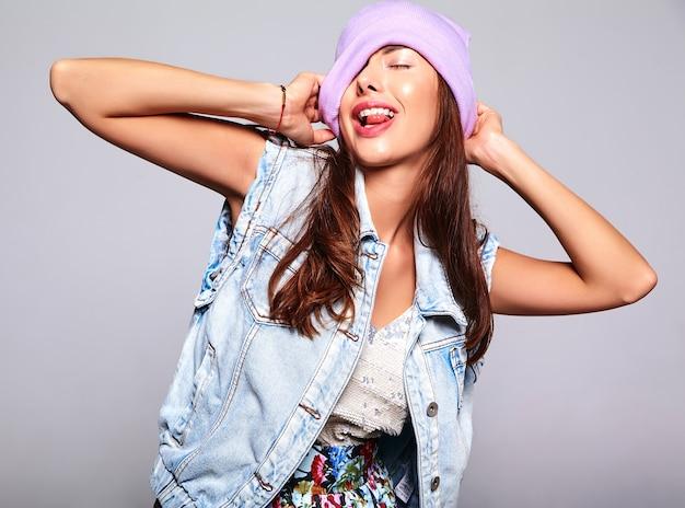 O retrato do modelo moreno bonito bonito da mulher em calças de brim ocasionais do verão veste-se sem a composição no gorro roxo isolado no cinza. mostrando a língua