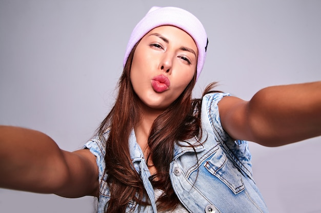 O retrato do modelo moreno bonito bonito da mulher em calças de brim ocasionais do verão veste-se sem a composição no gorro roxo que faz a foto do selfie no telefone isolado no cinza. dando beijo no ar