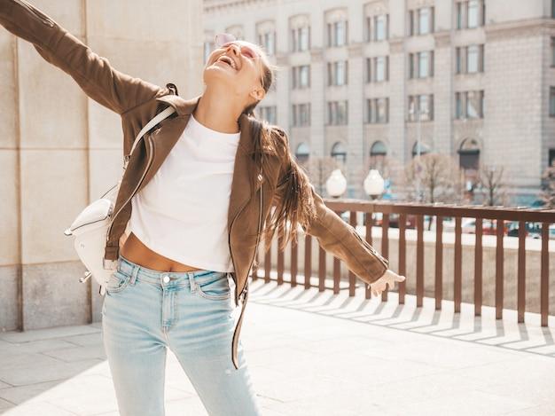 O retrato do modelo moreno sorridente bonito vestiu-se com roupas de jaqueta hipster de verão. . levantando as mãos