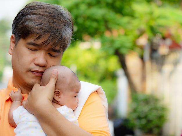 O retrato do pai feliz de ásia que prende seu bebê doce recém-nascido vestiu-se na roupa branca.