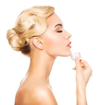 O retrato do perfil de uma mulher jovem e bonita com os olhos fechados aplica o gelo no rosto. isolado no branco.