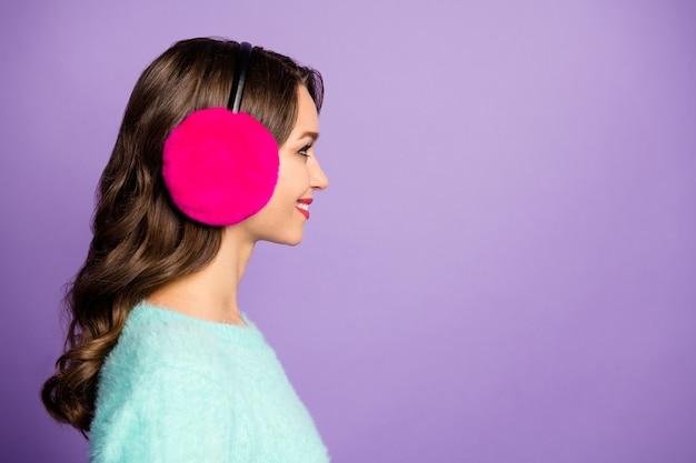 O retrato do perfil do close up da atraente senhora encaracolada dentuça sorrindo à procura do espaço vazio usa protetores de ouvido pastel quente rosa de pulôver macio difuso.