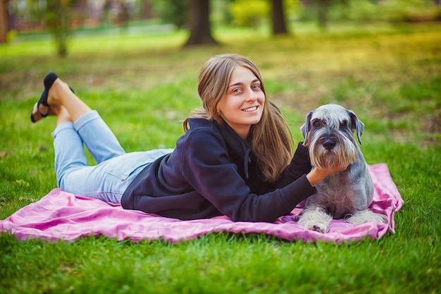 O retrato do proprietário e o cão áspero da collie apreciam, descansando e acariciando junto na rua da cidade.