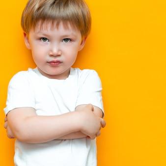 O retrato do rapaz pequeno irritado com braços dobrou-se isolado. criança triste e infeliz. menino da criança chateado