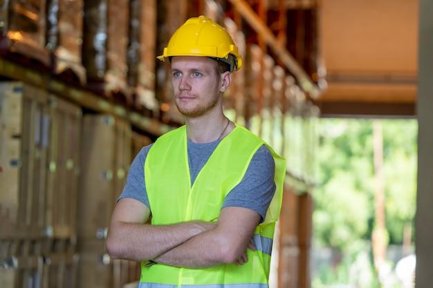 O retrato do trabalhador do armazém que está com braços cruzou-se na fábrica.