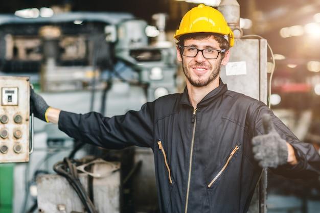 O retrato do trabalhador feliz americano novo aprecia o sorriso feliz para trabalhar em uma fábrica industrial pesada.
