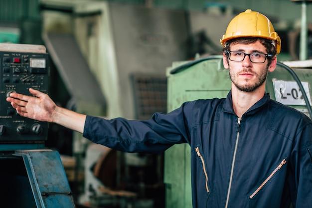 O retrato do trabalhador feliz americano novo aprecia o sorriso feliz para trabalhar em uma postura industrial pesada de factory.hand atual.