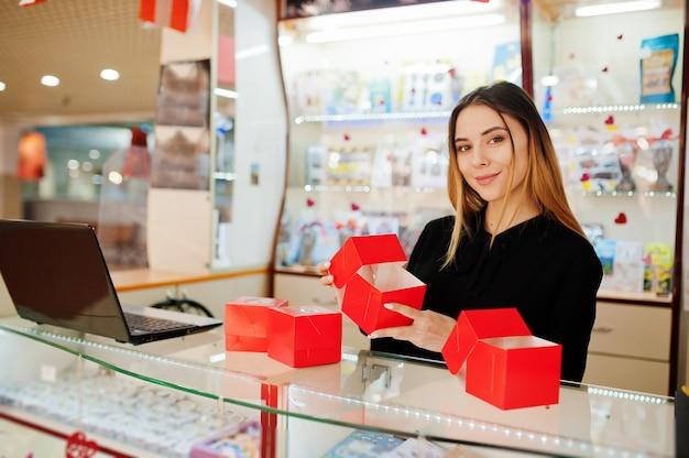O retrato do vendedor caucasiano fêmea novo prende caixas de presente vermelhas. empresa de pequeno porte de loja de lembranças de doces.
