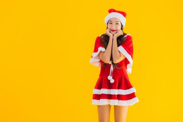 O retrato e o chapéu e as roupas asiáticos novos bonitos do natal da mulher sorriem feliz