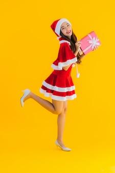 O retrato e o chapéu e as roupas asiáticos novos bonitos do natal sorriem felizes com caixa de presente vermelha