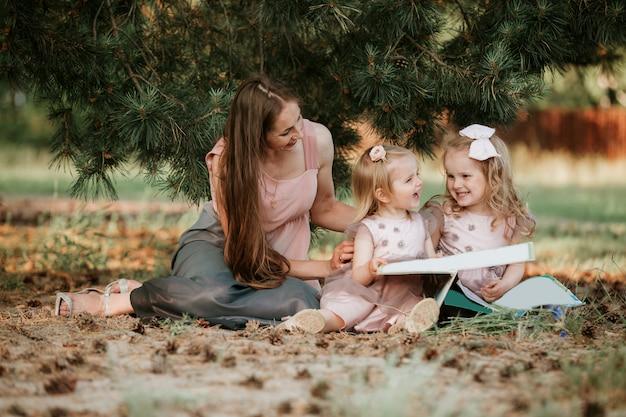 O retrato exterior de duas meninas está lendo um livro na grama com mãe. ela tem uma expressão de prazer e parecia muito relaxada nos braços da mãe.