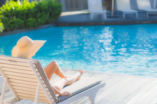 O retrato feliz asiático novo bonito da mulher relaxa em torno da piscina exterior no recurso do hotel