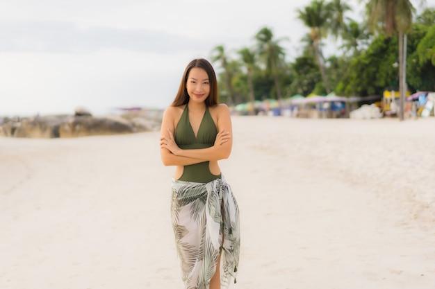 O retrato feliz mulheres asiáticas sorriso feliz relaxa no oceano tropical do mar da praia