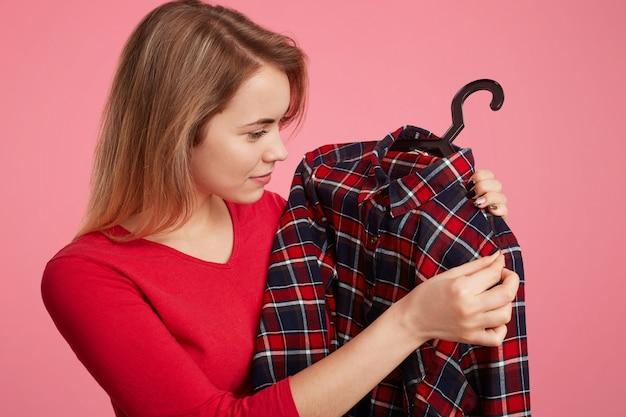O retrato lateral da fêmea jovem de aparência agradável escolhe uma roupa nova, olha a camisa quadriculada em cabides, alegra-se a nova compra