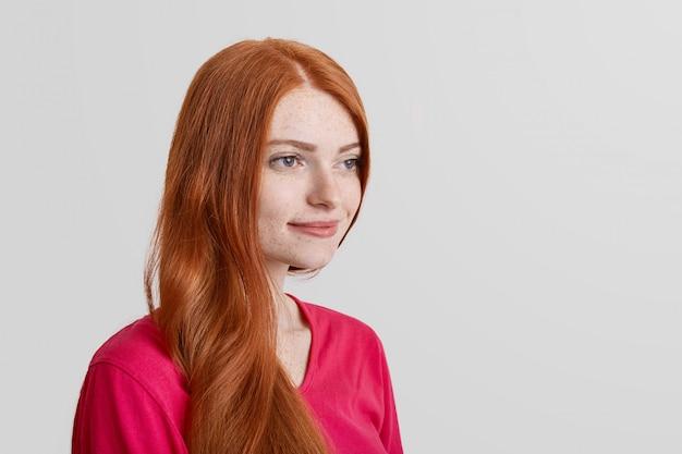 O retrato lateral do modelo feminino de gengibre sardento pensativo lembra alguns momentos agradáveis da vida, olha com expressão positiva para a distância, isolado no branco com espaço da cópia