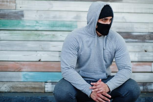 O retrato ostenta o homem árabe na máscara protetora médica preta e no hoodie durante a quarentena do coronavírus.