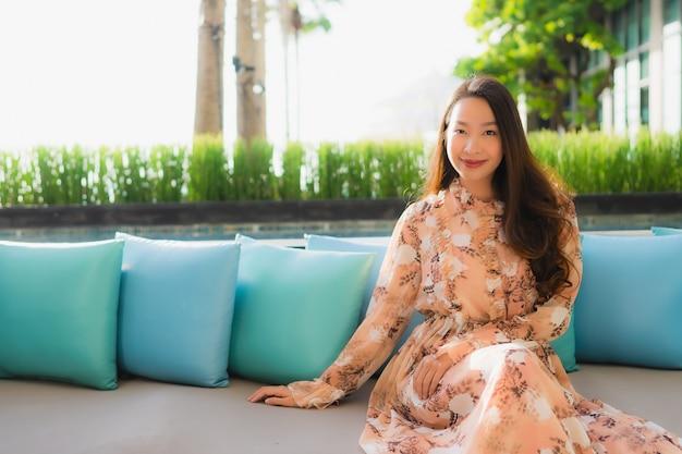O retrato que as mulheres asiáticas novas bonitas sorriem feliz senta-se no sofá em torno de exterior