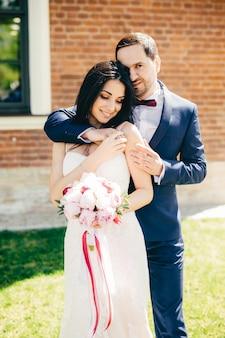 O retrato vertical da morena jovem encantadora noiva vestida de branco, recebe o abraço do noivo afetuoso,