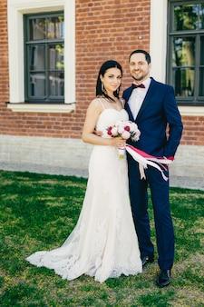 O retrato vertical da noiva e do noivo felizes fica ao lado do outro, espera pelos convidados, comemora seu casamento