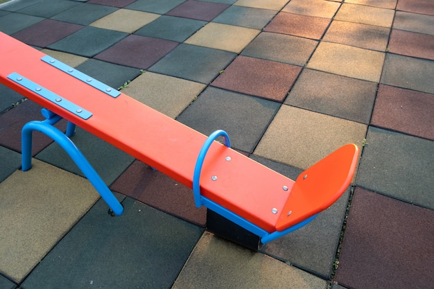 O revestimento de borracha e a aleta oscilam no playground da pré-escola.