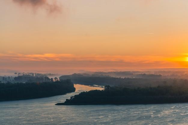 O rio corre ao longo da costa com a floresta sob a névoa. brilho laranja no céu do amanhecer refletido na água.