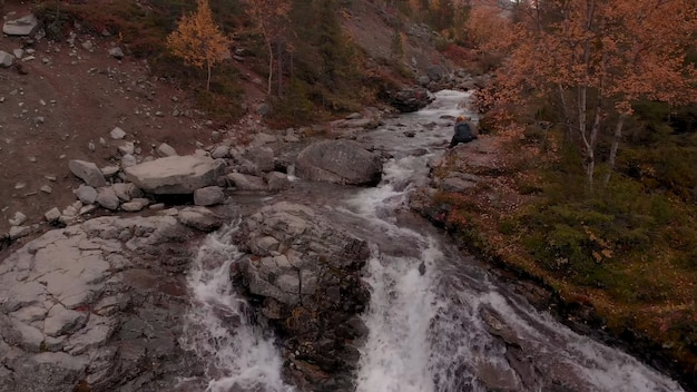O rio da montanha desce pelas corredeiras de granito, folhas amareladas de outono nas árvores