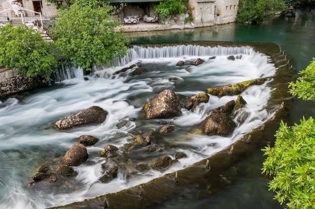 O rio da montanha formou uma pequena cachoeira entre as corredeiras rochosas.