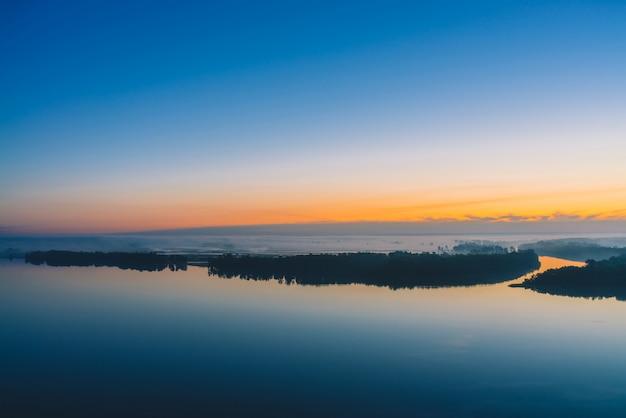 O rio largo corre ao longo da costa diagonal com a floresta sob uma névoa espessa. céu azul adiantado refletido na água. brilho amarelo no céu pitoresco antes do amanhecer.