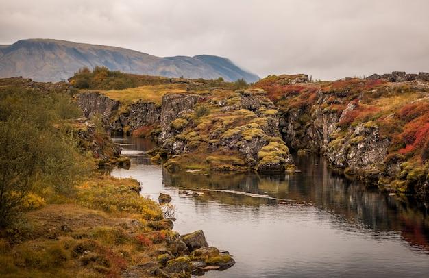 O rio que flui através das rochas capturadas no parque nacional thingvellir, na islândia