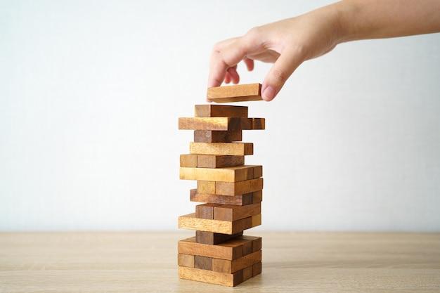 O risco vai acontecer. mão do engenheiro jogando um jogo de blocos de madeira em tom vintage de mesa de madeira.