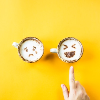 O riso e a tristeza de emoji são desenhados em xícaras de cappuccino em um fundo amarelo