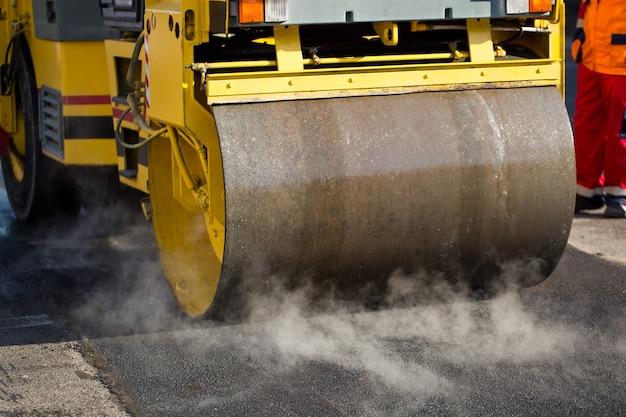 O rolo compressor compacto aplaina o asfalto