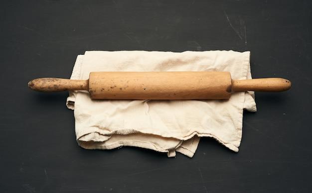 O rolo de madeira repousa sobre um guardanapo de linho cinza, mesa preta