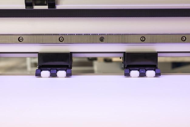 O rolo do papel vazio e roda dentro a grande máquina de jato de tinta do formato da impressora para o negócio industrial.