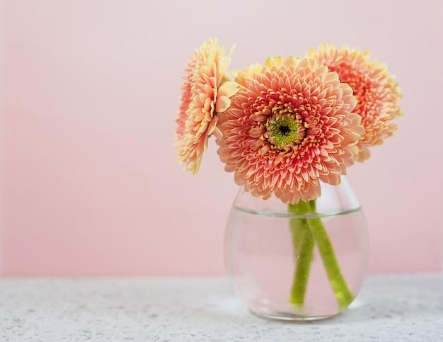 O rosa bonito da mola floresce na tabela pastel azul em um vaso. borda floral.