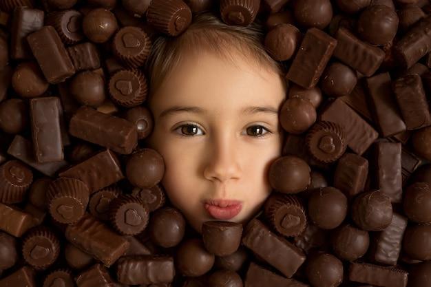 O rosto da menina em um fundo de chocolates. o consumo excessivo de doces é prejudicial à saúde