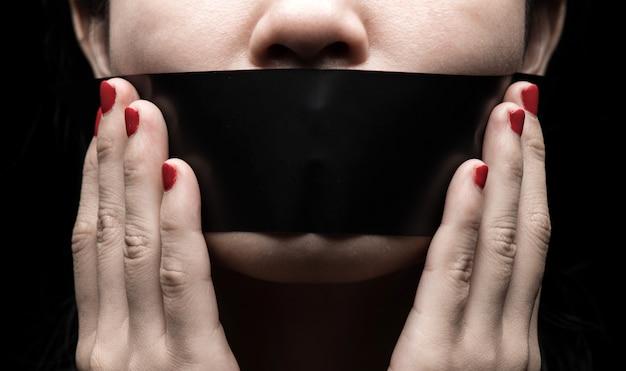O rosto da menina está selado a boca com papel preto