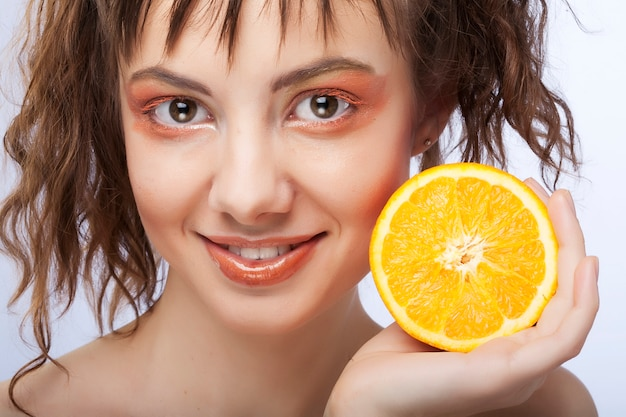O rosto de mulher com laranja suculenta